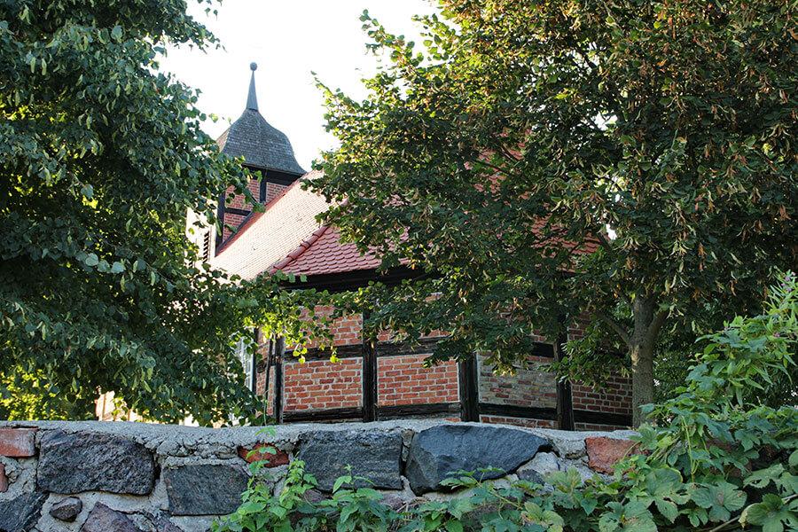 Krugsdorf - Dorfkirche Ansicht durch Bäume über die kleine Feldsteinmauer