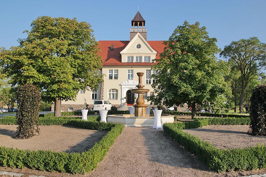 Krugsdorf - Schloss Krugsdorf - Anlage mit Brunnen und verzierter Eingangsberiech