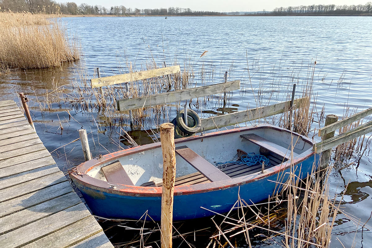 Koblentz - Kleiner Koblentzer See - Anlegestelle mit einem kleinen blauen Ruderboot, direkt am Holzsteg