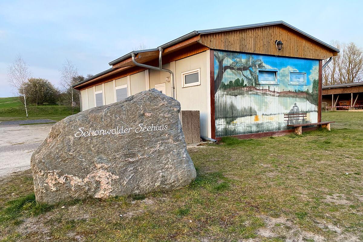 """Schönwalde - Schönwalder Seehaus mit kunstvoll bemalter Seitenansicht und großem Findling mit der Aufschrift """"Schönwalder Seehaus"""""""