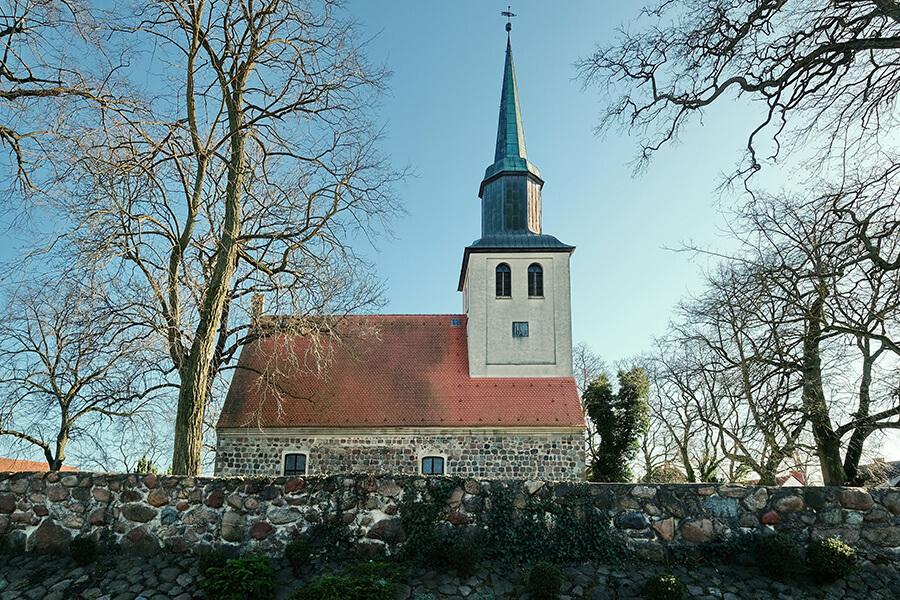 Groß Luckow - Dorfkirche mit Blick auf die Steinmauer