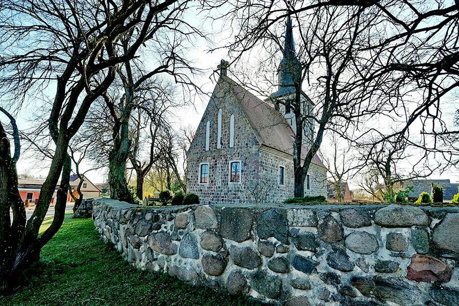 Groß Luckow - Blick über die Steinmauer auf die Kirche und den Friedhof